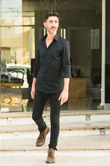 Портрет мужчины в черной рубашке и джинсах, стоящих перед стеклянной дверью