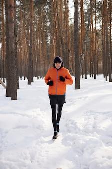 Портрет мужчины в яркой спортивной одежде, бегущего по зимнему лесу. морозный день