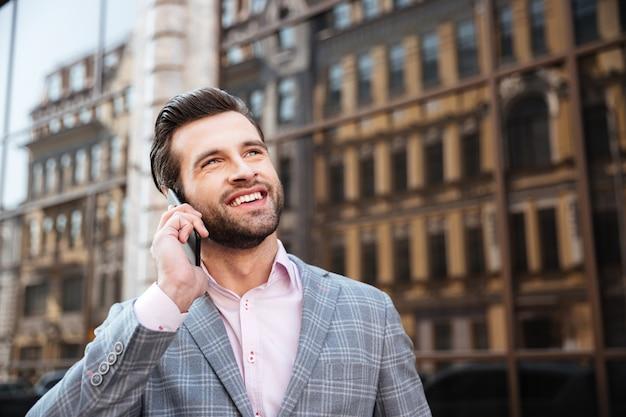 Портрет мужчины в куртке разговаривает по мобильному телефону