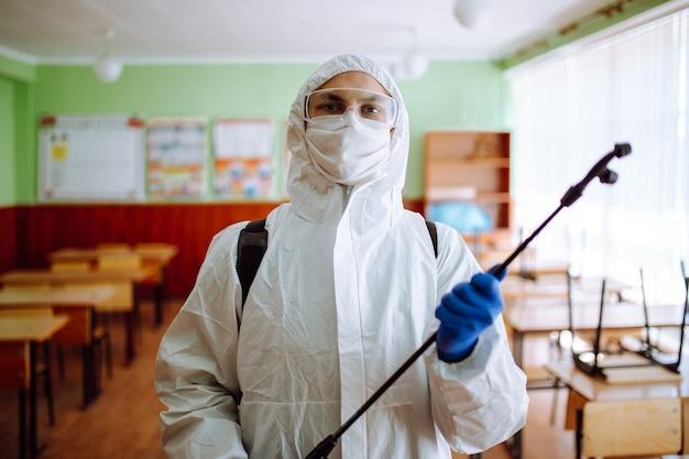 살균제 스프레이로 교실을 청소하는 보호용 항균복을 입은 남자의 초상화. 전문 위생 작업자가 특수 장비로 강당을 소독합니다.