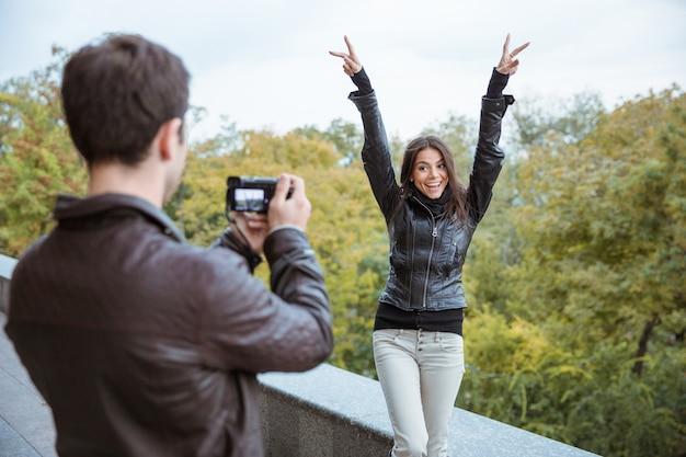 Портрет мужчины, фотографирующего смешную женщину на открытом воздухе