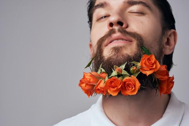ひげのファッションのクローズアップで花をポーズする男の肖像画