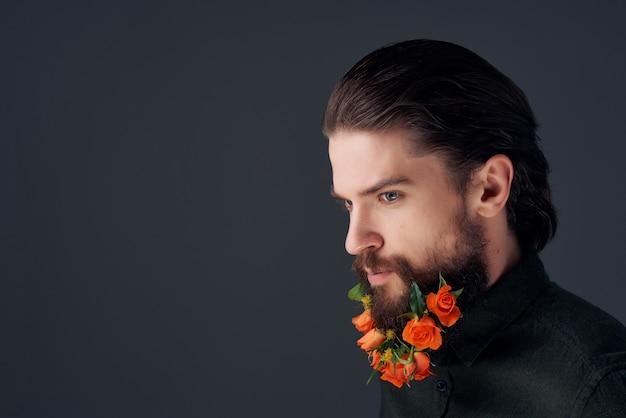 ひげのファッションの暗い背景で花をポーズする男の肖像画。高品質の写真