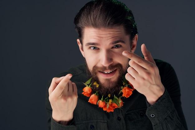ひげのファッションの暗い背景で花をポーズする男の肖像画