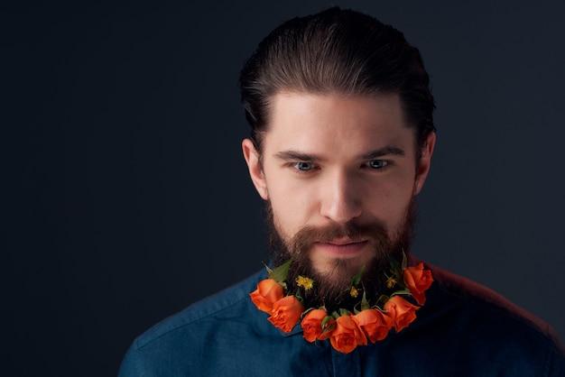 ひげファッションライフスタイルクローズアップスタジオで花をポーズする男の肖像画