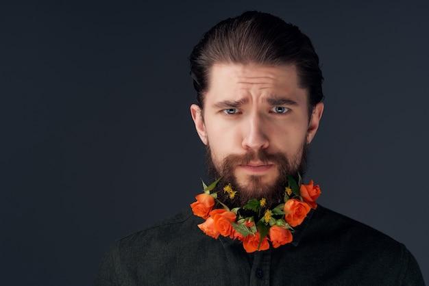 ひげのファッションスタジオのライフスタイルで花をポーズする男の肖像画
