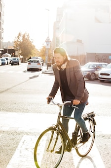 Portrait of a man riding bicycle on city road in sunlight