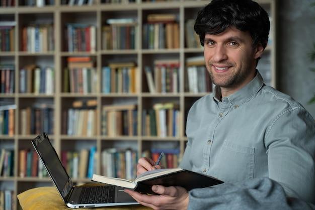 Портрет мужчины, сидящего на диване с ноутбуком на книжной полке