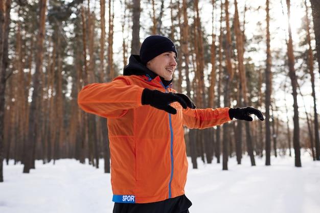 Портрет мужчины, растягивающегося в парке в прекрасный снежный зимний день, готовящегося к бегу