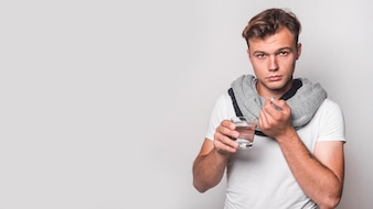 Portrait of a man taking capsule with water on white background