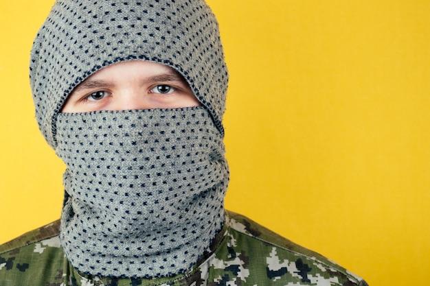 カモフラージュとマスクの男のテロリストの肖像画。匿名性とテロリズムの概念。