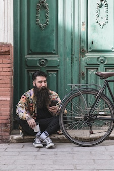 Портрет мужчины с помощью мобильного телефона сидит возле велосипеда перед зеленой деревянной дверью
