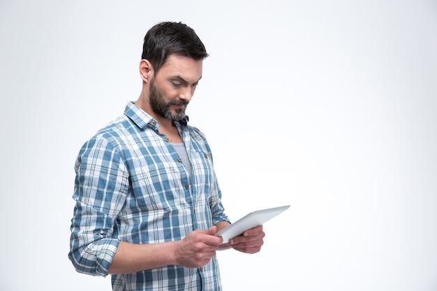 白い壁に分離されたタブレットコンピューターを使用して男の肖像画