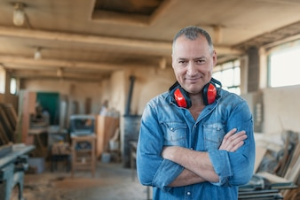 Portrait of a man who owns a small carpentry business, standing in his workshop