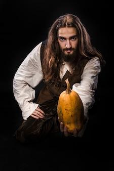 黒い壁に中世の海賊の衣装、熟したカボチャを保持している海賊を身に着けているひげと長い髪を持つ男の肖像