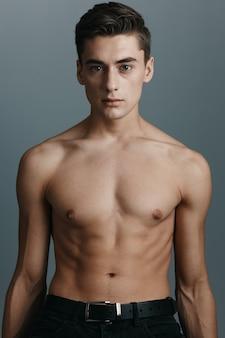 Портрет мужчины с голым торсом на сером фоне крупным планом брюнет обрезанный вид. фото высокого качества