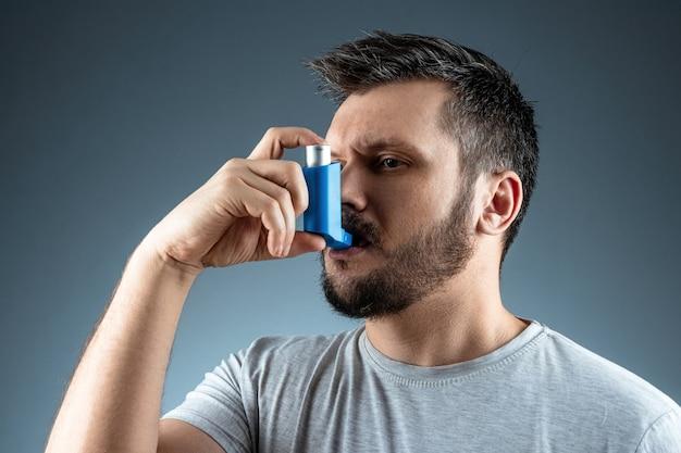 彼の手に喘息吸入器、喘息発作を持つ男の肖像。気管支喘息、咳、アレルギー、呼吸困難の治療の概念。