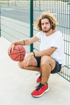 Portrait of a man with basketball in court