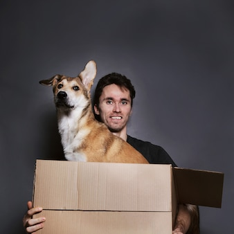 灰色の背景に大きな移動ボックスとかわいい雑種犬の中に男の肖像画