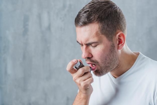 천식 흡입기를 사용하여 닫힌 눈을 가진 남자의 초상