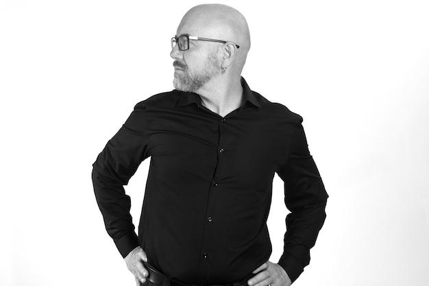 白い背景の上のシャツと腰に手と眼鏡の側を持つ男の肖像画