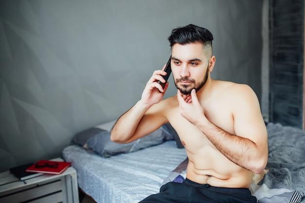 침실에서 스마트폰을 사용하는 피트니스 몸을 가진 남자의 초상화.