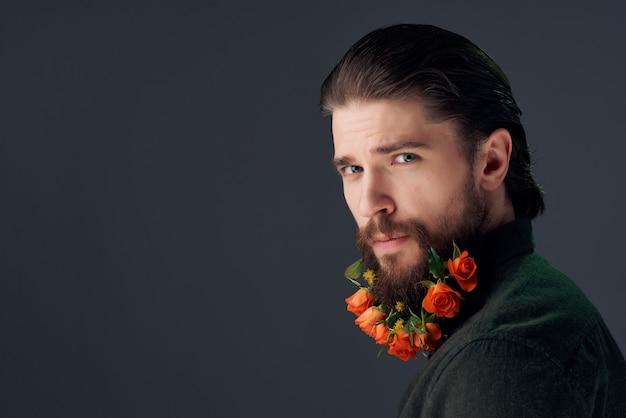格子縞のシャツのクローズアップスタジオでひげに花を持つ男の肖像画
