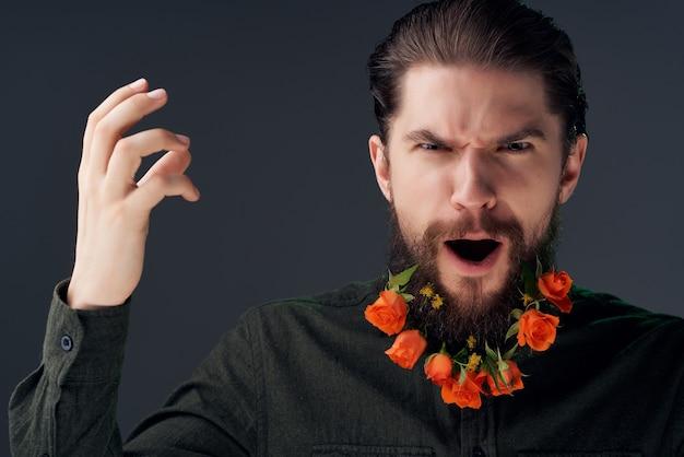 シャツのクローズアップでひげに花を持つ男の肖像画。高品質の写真