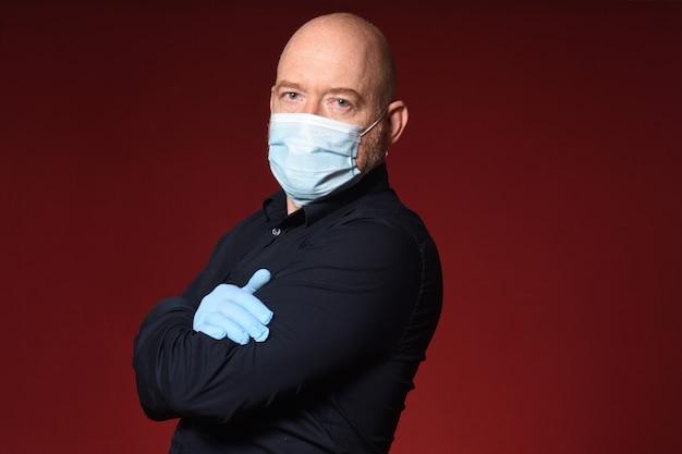 赤い背景に交差した手袋とマスクの腕を持つ男の肖像画