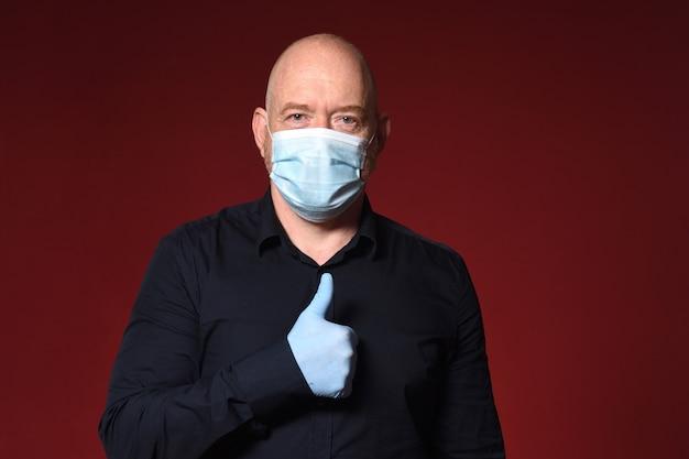 Портрет мужчины в перчатках и маске показывает палец вверх на красном фоне