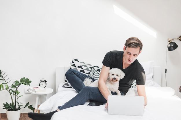 Портрет человека с его игрушечным пуделем, используя ноутбук в спальне