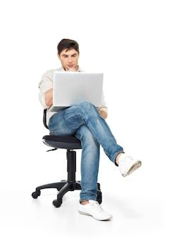 Портрет мужчины, работающего на ноутбуке, сидя на стуле