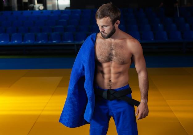 Портрет мастера единоборств в синем кимоно и черном поясе с голым торсом в спортивном зале
