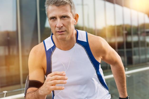 イヤホンでジョギング中年の男性アスリートの肖像