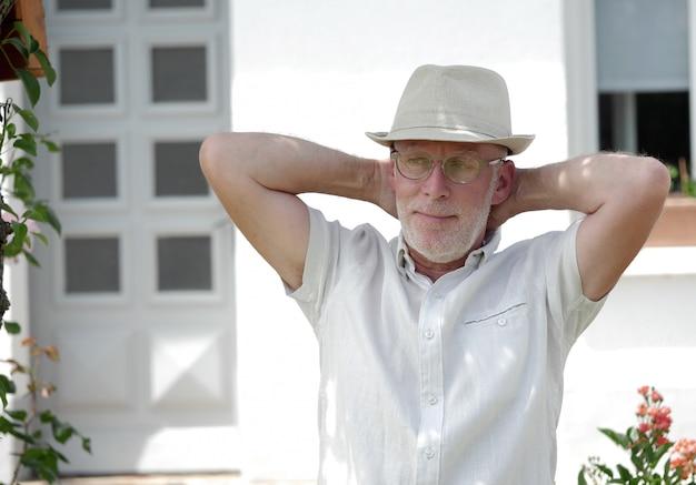 Портрет зрелого человека, расслабляющий в саду
