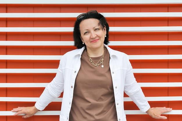 白い縞模様の明るいオレンジ色の背景に夏服を着た成熟した笑顔の女性の肖像画。