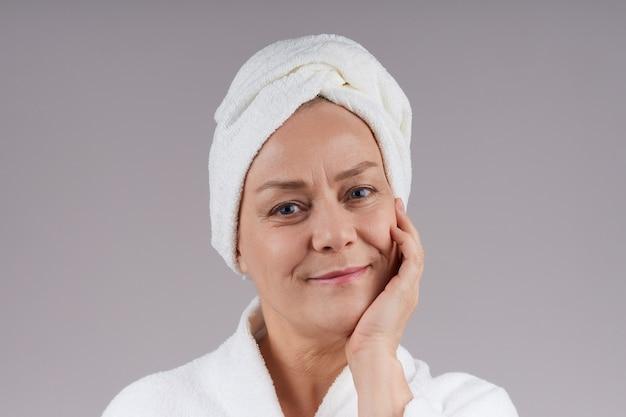 彼女の頭にタオルでバスローブを着た成熟した女性の肖像画。ボディケアのコンセプト。灰色の壁に隔離します。