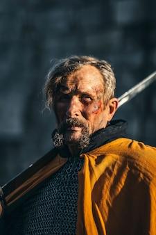 彼の顔に血との戦いの後の鎧で中世の上級戦士の肖像画。戦士は手に剣を持っている