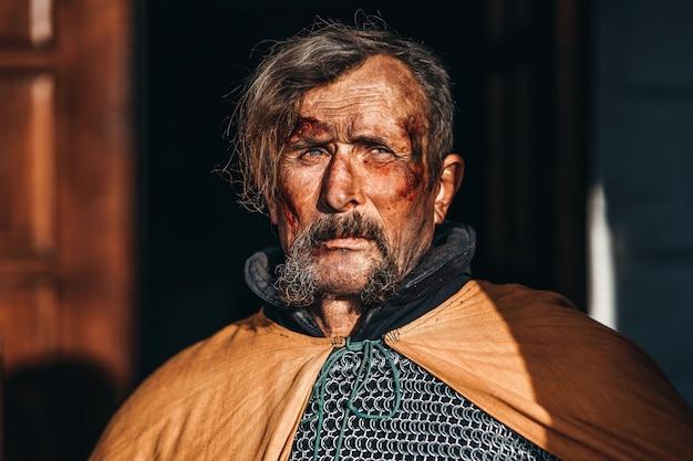 汚れた血まみれの顔との戦いの後の鎧で中世の上級戦士の男の肖像