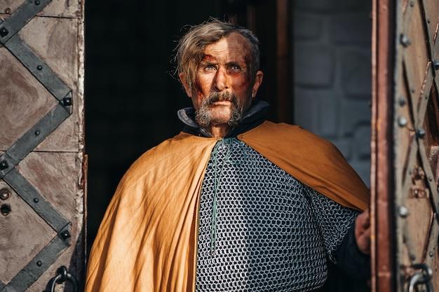 Портрет средневекового старшего воина в доспехах после битвы с грязным и замазанным кровью лицом