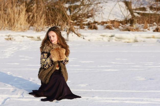 Портрет средневековой девушки-викинга в длинном платье зимой