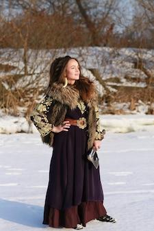 Портрет средневековой девушки-викинга в длинном платье с топором в зимнем лесу