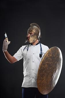 注射器を保持しているヘルメットの中世の戦士の医者の肖像画