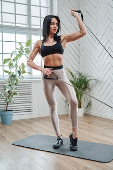 明るい部屋で抵抗バンドで運動を練習している黒い髪の中年のスポーツ女性の肖像画。