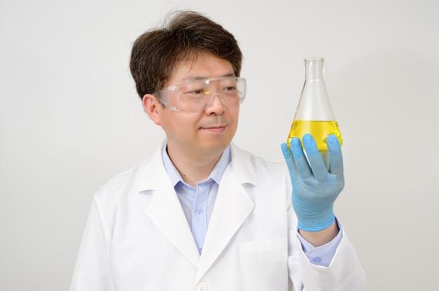 白い実験用ガウンと手袋を着用し、実験用コンテナを手に持っている中年のアジア人男性科学者の肖像画。