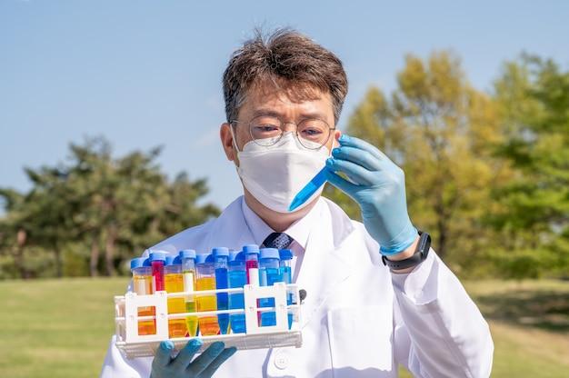 白い白衣と手袋を着用し、実験用容器を手に持った中年のアジア人男性科学者の肖像画。