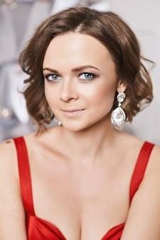 Портрет девушки модели с ярким макияжем и модными серьгами в красном платье.