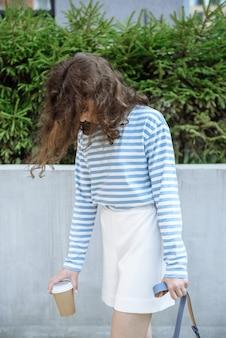 도시 거리 카탈로그의 배경에 있는 새로운 여름 옷 컬렉션에서 포즈를 취한 모델의 초상화