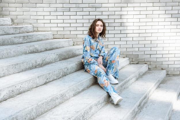 계단에 앉아서 새로운 옷 컬렉션에서 포즈를 취하는 모델 여성의 초상화