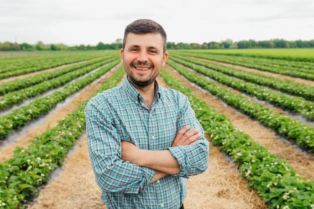 Портрет современного бородатого фермера со скрещенными руками, смотрящего в камеру, стоит в сельскохозяйственном поле, веселый рабочий-мужчина в сельскохозяйственной ферме, сельском хозяйстве